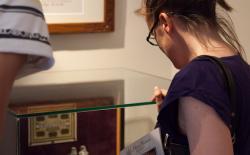 Bezoekers bewonderen een negentiende-eeuwse medicijnflessen houder